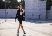 Young businesswoman walking outdoors 11015306993| 写真素材・ストックフォト・画像・イラスト素材|アマナイメージズ