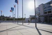 Young businesswoman walking outdoors, walking past European flags 11015306994| 写真素材・ストックフォト・画像・イラスト素材|アマナイメージズ