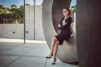Portrait of young businesswoman sitting outdoors, arms folded 11015306995| 写真素材・ストックフォト・画像・イラスト素材|アマナイメージズ