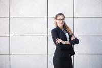 Portrait of young businesswoman, arms folded 11015306996| 写真素材・ストックフォト・画像・イラスト素材|アマナイメージズ