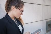 Young businesswoman using smartphone, outdoors 11015306997| 写真素材・ストックフォト・画像・イラスト素材|アマナイメージズ