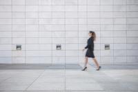 Young businesswoman walking outdoors, blurred motion 11015306999| 写真素材・ストックフォト・画像・イラスト素材|アマナイメージズ