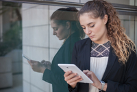 Young businesswoman, standing outdoors, beside window, using digital tablet 11015307002| 写真素材・ストックフォト・画像・イラスト素材|アマナイメージズ