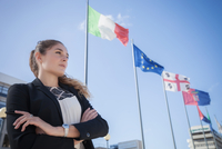 Portrait of young businesswoman, outdoors, arms folded, European flags flying in background 11015307003| 写真素材・ストックフォト・画像・イラスト素材|アマナイメージズ