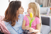 Girl handing tulip to mother and puckering lips on sofa