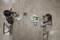 Overhead portrait of girl and brother eating dinner at kitchen table 11015307143| 写真素材・ストックフォト・画像・イラスト素材|アマナイメージズ