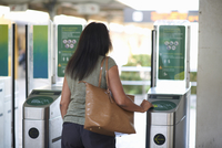 Rear view of woman using ticket touchscreen at railway ticket barrier 11015307251| 写真素材・ストックフォト・画像・イラスト素材|アマナイメージズ