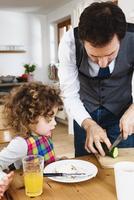 Man slicing cucumber for daughter sitting at table 11015307524| 写真素材・ストックフォト・画像・イラスト素材|アマナイメージズ