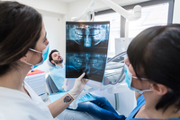 Female dentist and dental nurse looking at dental x-ray