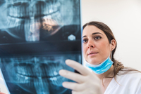 Female dentist looking at dental x-ray