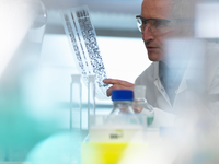 Researcher holding a DNA (deoxyribonucleic acid) gel during a genetic experiment in a laboratory 11015307592| 写真素材・ストックフォト・画像・イラスト素材|アマナイメージズ