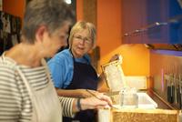 Two senior female beekeepers scraping honeycombs in kitchen 11015307874| 写真素材・ストックフォト・画像・イラスト素材|アマナイメージズ