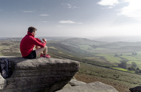 Male runner sitting looking out from top of Stanage Edge, Peak District, Derbyshire, UK