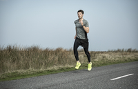 Male runner running along rural moorland road