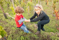 Boy giving mother a helping hand in vineyard