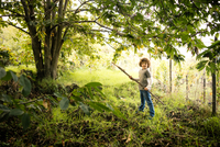 Portrait of boy with pole to collect chestnuts in vineyard woods