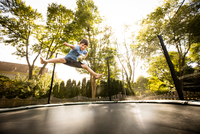 Young boy jumping on large trampoline, low angle view
