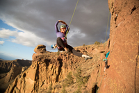 Female rock climber swinging out on rope, Smith Rock State Park, Oregon, USA