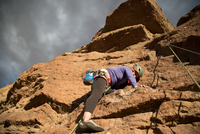 Female rock climber climbing mountain, low angle view, Smith Rock State Park, Oregon, USA
