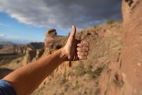 Rock climber giving thumbs up sign, close-up, Smith Rock State Park, Oregon, USA