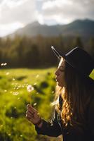 Woman blowing dandelion seeds, Rocky Mountain National Park, Colorado, USA 11015308324| 写真素材・ストックフォト・画像・イラスト素材|アマナイメージズ