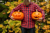 Mature man holding carved pumpkins 11015308341| 写真素材・ストックフォト・画像・イラスト素材|アマナイメージズ