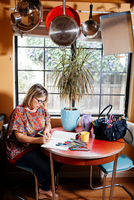 Woman at dining table coloring in