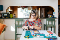 Woman at dining table creating scrapbook