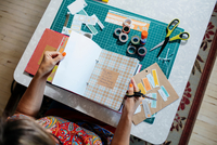 High angle view of woman at dining table creating scrapbook
