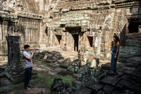Couple taking photograph in Angkor Wat temple, Siem Reap, Cambodia