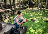 Man crouching holding smartphone, Phimeanakas temple, Siem Reap, Cambodia