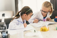Girls doing science experiments writing in notebooks 11015308409| 写真素材・ストックフォト・画像・イラスト素材|アマナイメージズ