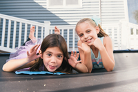 Girls lying on trampoline looking at camera making faces