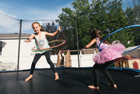 Girls with hula hoops jumping on trampoline