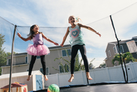 Girls in mid air jumping on trampoline