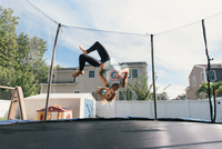 Girl upside down in mid air, jumping on trampoline