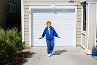 Senior woman skipping in front of garage door 11015308594| 写真素材・ストックフォト・画像・イラスト素材|アマナイメージズ