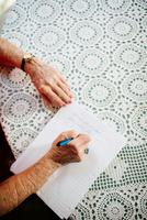 Senior woman writing at dining table, close-up of hands 11015308603| 写真素材・ストックフォト・画像・イラスト素材|アマナイメージズ