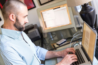 Mid adult man typing on laptop, working at home 11015308751| 写真素材・ストックフォト・画像・イラスト素材|アマナイメージズ