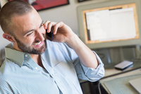 Mid adult man talking on smartphone, working at home 11015308752| 写真素材・ストックフォト・画像・イラスト素材|アマナイメージズ