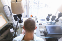 Rear view of man typing on laptop, working at home 11015308761| 写真素材・ストックフォト・画像・イラスト素材|アマナイメージズ