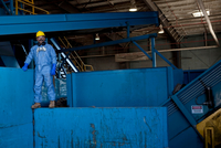Portrait of male worker in hard hat standing on blue heavy machinery at recycling plant 11015308784| 写真素材・ストックフォト・画像・イラスト素材|アマナイメージズ