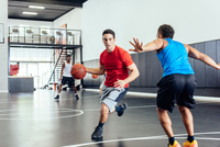Two male basketball players practicing running and defending ball on basketball court