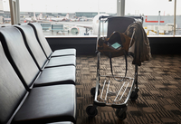Smartphone in shoulder bag in luggage trolley in airport lounge