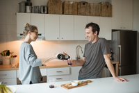 Mid adult couple pouring red wine in kitchen