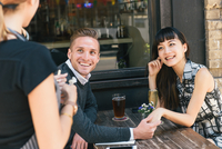 Waitress serving young couple outside restaurant 11015309516| 写真素材・ストックフォト・画像・イラスト素材|アマナイメージズ
