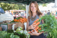 Woman at fruit and vegetable stall holding carrots 11015309560| 写真素材・ストックフォト・画像・イラスト素材|アマナイメージズ
