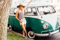Woman by vintage camper van looking at camera 11015309701| 写真素材・ストックフォト・画像・イラスト素材|アマナイメージズ