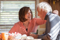 Senior couple laughing together at kitchen table