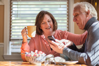 Senior couple looking at smartphone update at kitchen table